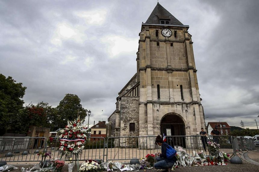 People pay tribute at a makeshift memorial near the Saint Etienne church, where priest Jacques Hamel was killed.