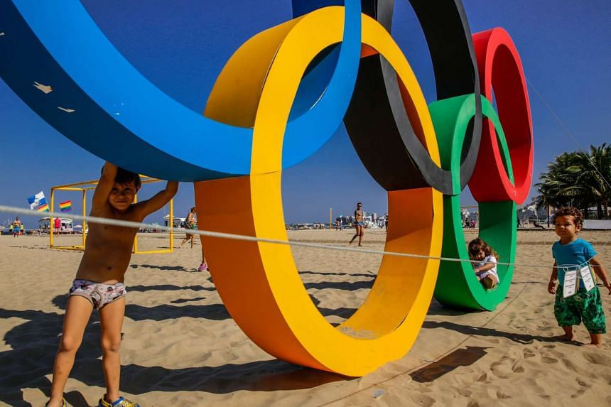Children play near a set of the Olympic rings, created from recycled material, on Copacabana beach in Rio de Janeiro, Brazil on July 27.