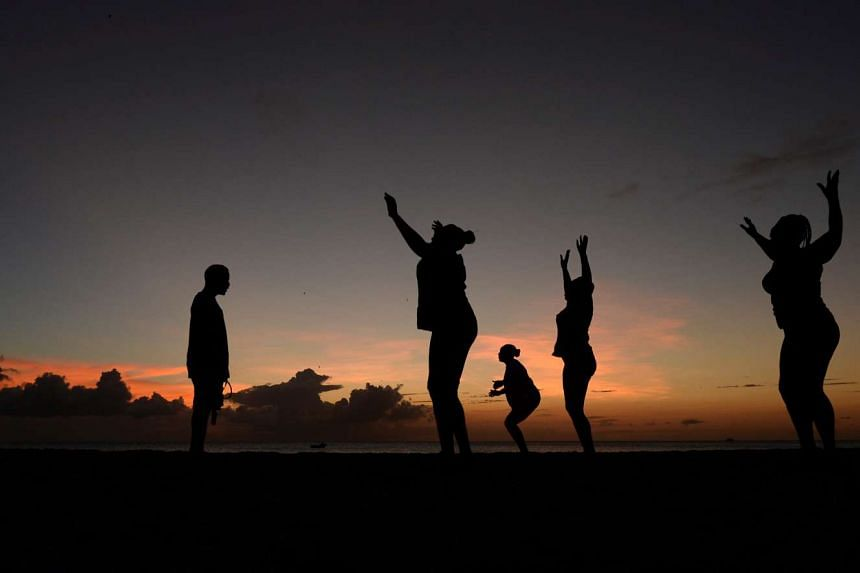 Women exercise in front of a trainer (left) as the sun sets near Kensington Oval in Bridgetown, Barbados on March 13, 2014.