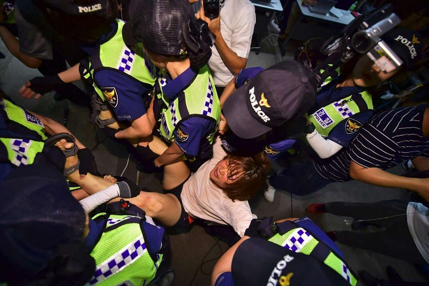 """Police take away a South Korean protester occupying the venue as the protesters denounce a deal between Seoul and Tokyo on resolving a long-running row over """"comfort women""""."""