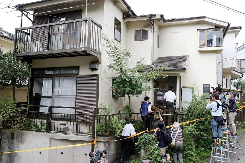 Police entering the house of Satoshi Uematsu yesterday while reporters and television crews stood outside. Uematsu had turned himself in at a police station after going on a killing spree on Tuesday.