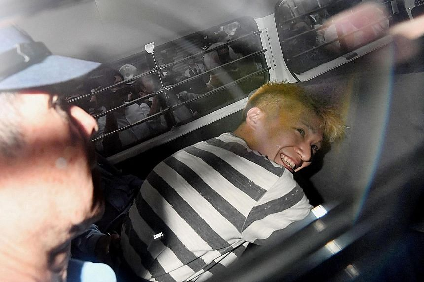 Uematsu smiling broadly as he sat inside a police vehicle, in this picture taken by Kyodo news agency yesterday.