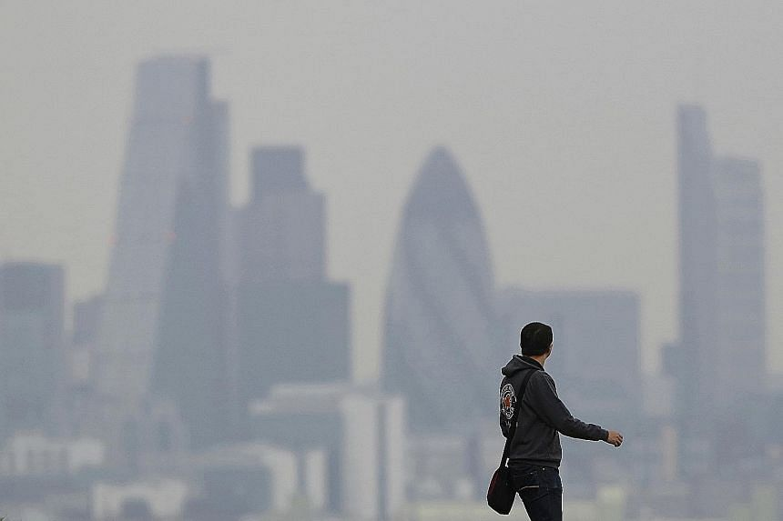 A man walks through Greenwich Park as haze sits over the London skyline in 2014.
