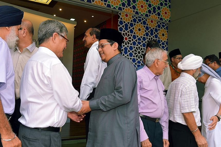 The Mufti of Singapore, Dr Fatris Bakaram (in grey), greeting leaders of Singapore's major faiths at a tea reception, in celebration of Hari Raya Puasa, at the Harmony Centre in Bishan yesterday.