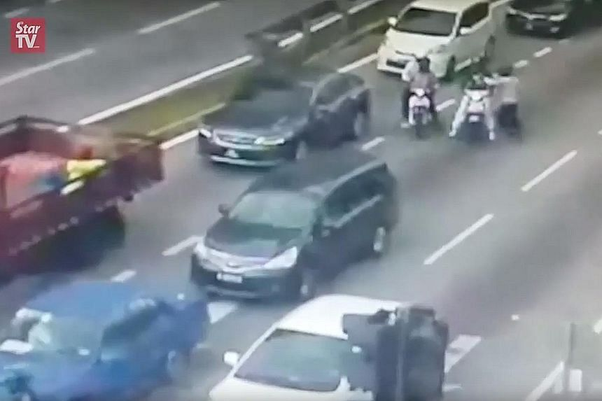 Video screenshots show four men on two motorcycles approaching the victim's car, which had stopped at a traffic light near Setapak Central mall in KL. Two of them fired the shots and they fled shortly after.