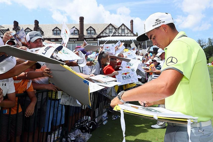 American Rickie Fowler signing autographs for fans during a practice round ahead of this week's PGA Championship.