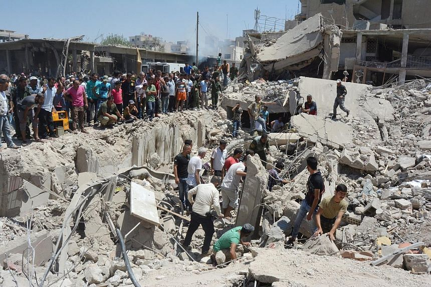 """People looking for survivors amid the ruins of a building destroyed by the blast in the Syrian city of Qamishli yesterday. ISIS said the bombing was revenge for """"crimes committed by crusader coalition aircraft""""."""