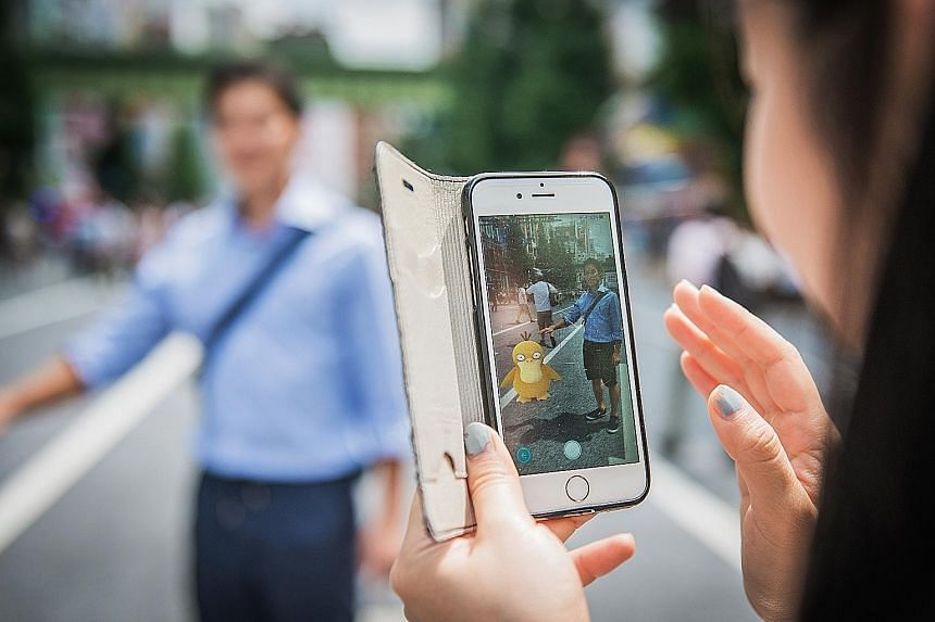 A woman plays the augmented- reality game Pokemon Go in Tokyo, Japan.