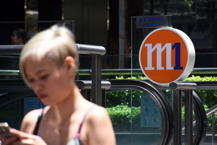 A woman walking past the M1 logo on Mar 15.