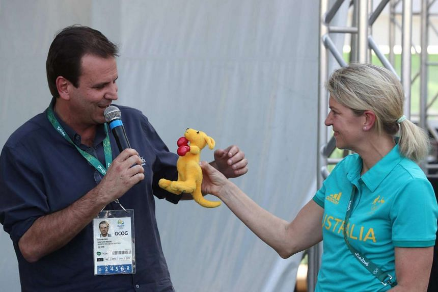 Mayor of Rio de Janeiro Eduardo Paes (left) accepts a kangaroo doll from the chief of the Olympic Australian Delegation Kitty Chiller (R) during a welcome ceremony.