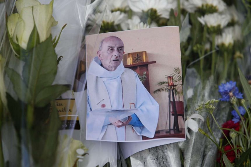 A photo of slain priest Jacques Hamel is seen amongst flowers at a makeshift memorial at the Saint-Etienne-du-Rouvray city hall in France.