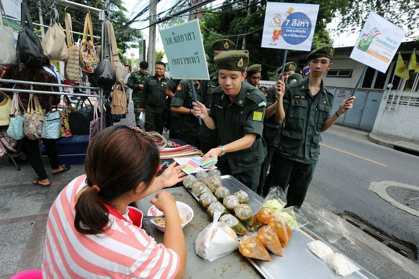 Thai Army Reserve Force volunteer students (right) hold placards as they hand out leaflets for a referendum campaign at a street market near Victory Monument in Bangkok, Thailand on July 27.