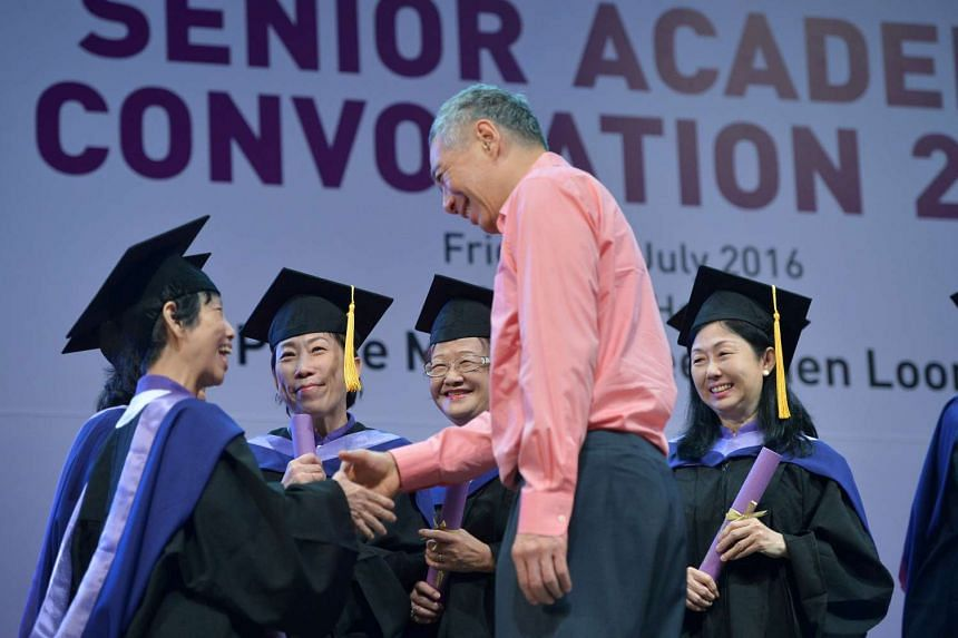 Prime Minister Lee Hsien Loong shakes hands with seniors graduating from the second batch of PA's Senior Academy at the Nanyang Polytechnic Auditorium.