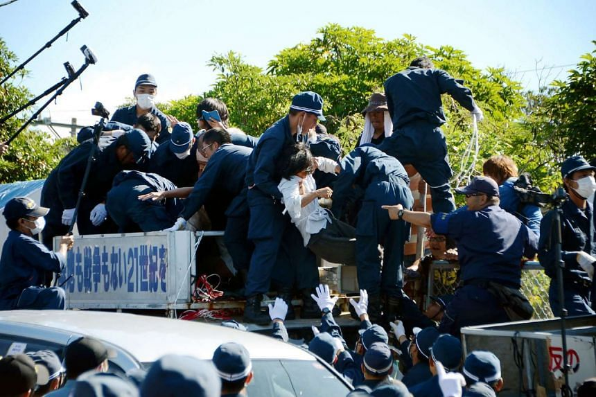 Protestors against the construction of helipads for US forces clash with riot police in Okinawa on July 22, 2016.