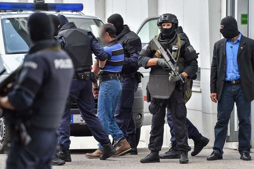 A man suspected of being involved in the November 2015 Paris terror attacks is led away by Austrian police from the court in Linz, Austria on July 27, 2016.
