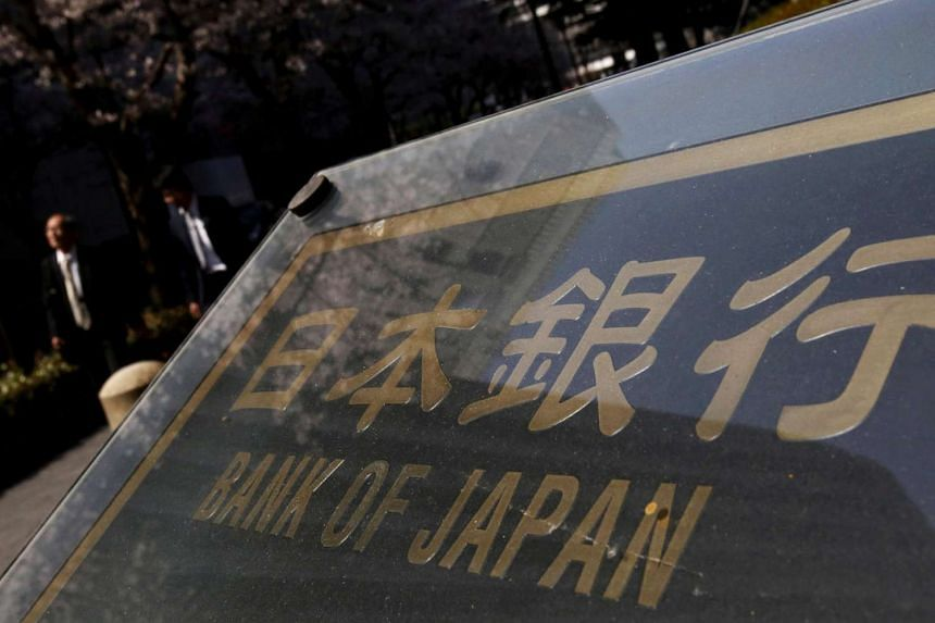 People walk along a street in front of the Bank of Japan headquarters in Tokyo, Japan on March 31.