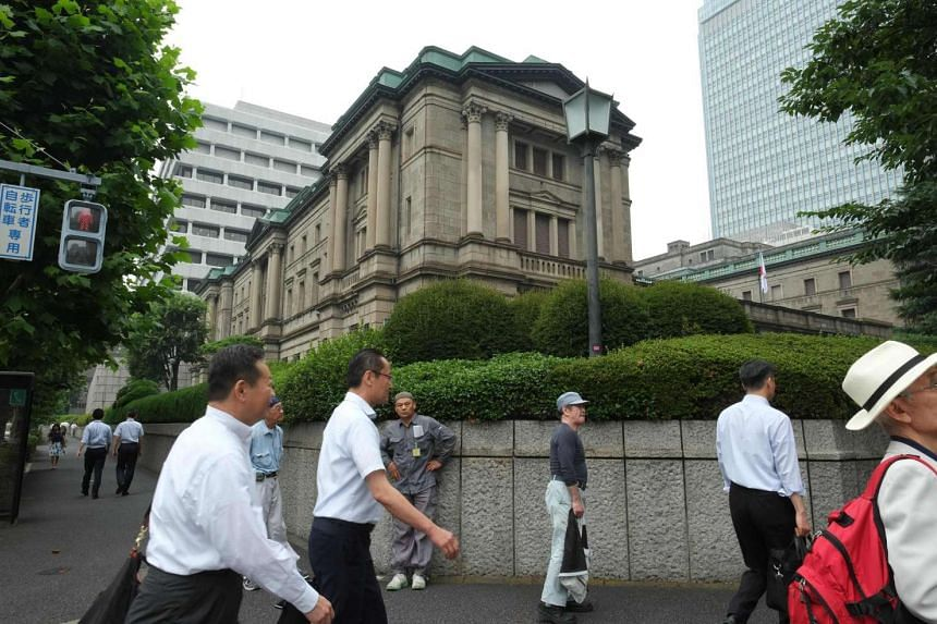 People walk in front of the Bank of Japan headquarters in Tokyo on July 1.