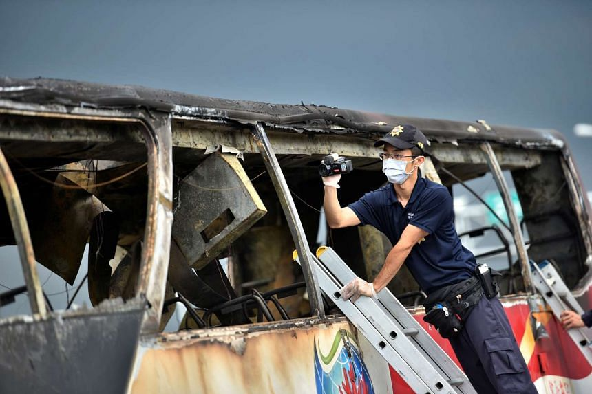 A policeman films the wreckage of a bus that crashed en route to Taoyuan airport, on July 19, 2016.