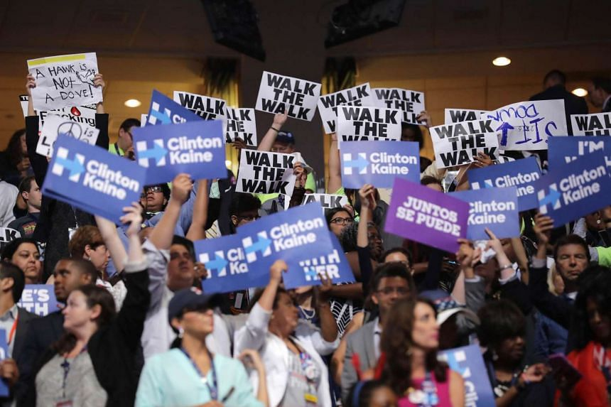 Delegates and attendees hold signs on the fourth day of the Democratic National Convention at the Wells Fargo Center on July 28 in Philadelphia, Pennsylvania.
