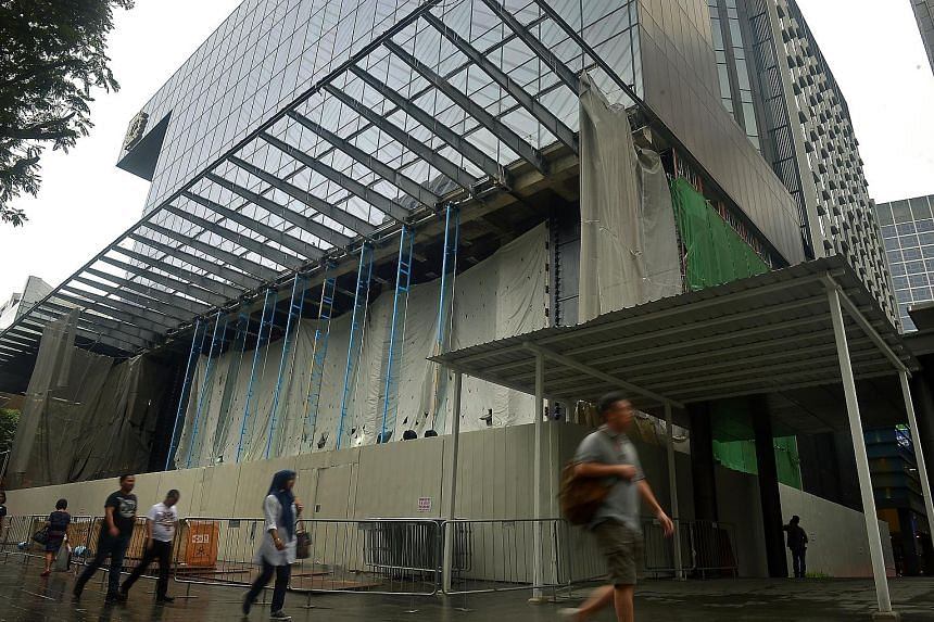 When The Straits Times visited the construction site at Knightsbridge mall (left) yesterday, the shop's interior was covered by construction canvas. However, tall glass structures were already in place, hinting at Apple's signature glass facade seen