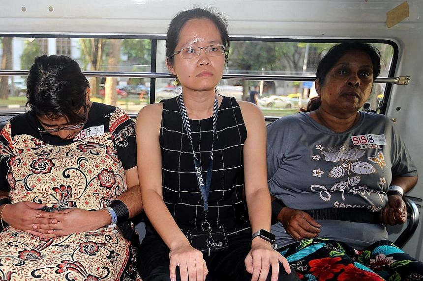 Gaiyathiri Murugayan (left) and her mother Prema Naraynasamy (right) - accompanied by a police officer - leaving for the Central Police Division in a police vehicle yesterday after they were charged with the murder of their domestic worker. The 36-ye