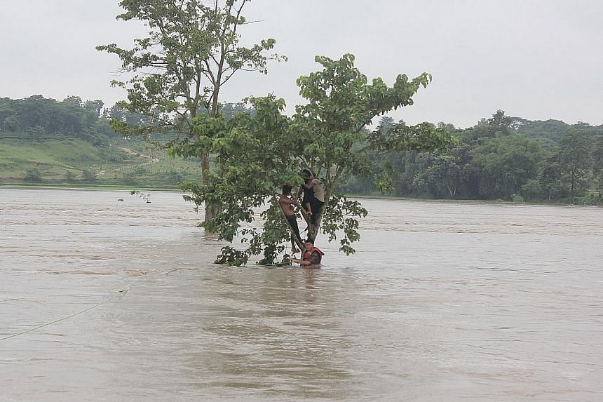 Flood victims in Jhapa, Nepal, taking refuge in a tree from the rising waters as a soldier offered them a rope in a rescue effort on Sunday.