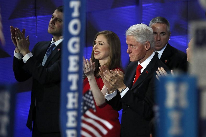 Former US President Bill Clinton, his daughter Chelsea and son-in-law Marc Mezvinsky applauding as Democratic US presidential nominee Hillary Clinton accepts the nomination on the final day of the Democratic National Convention in Philadelphia, Penns