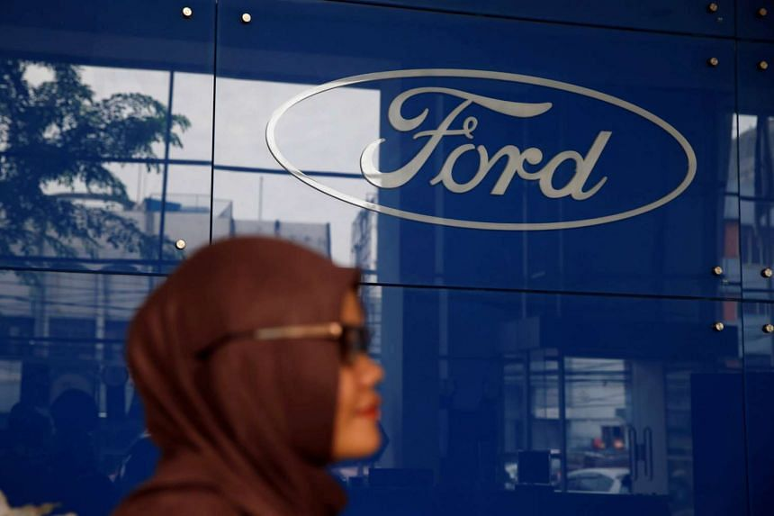A woman stands near a Ford logo at a dealership in Jakarta, Indonesia, on June 27, 2016.