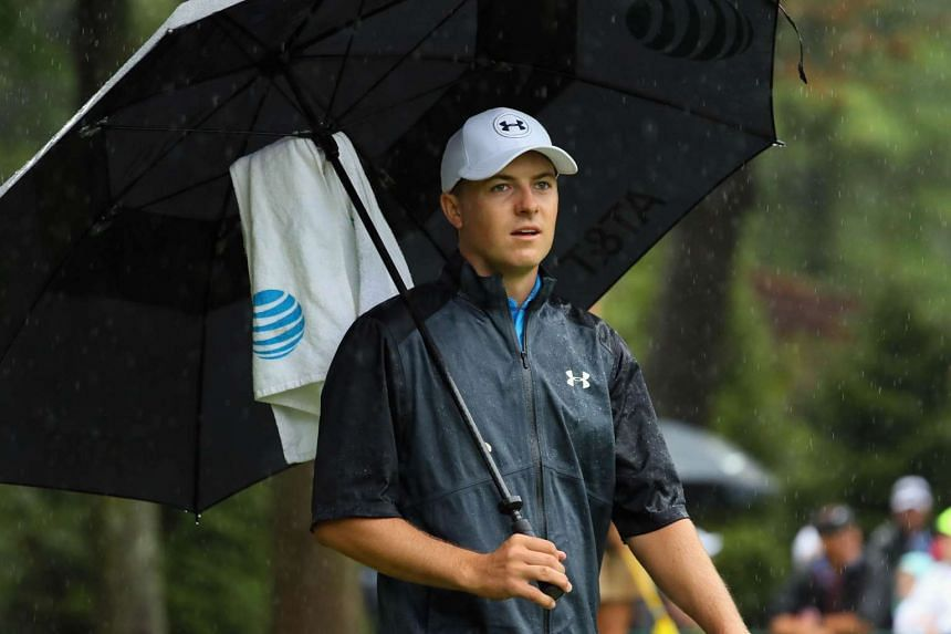 Spieth shelters under an umbrella on the 10th hole during the second round.