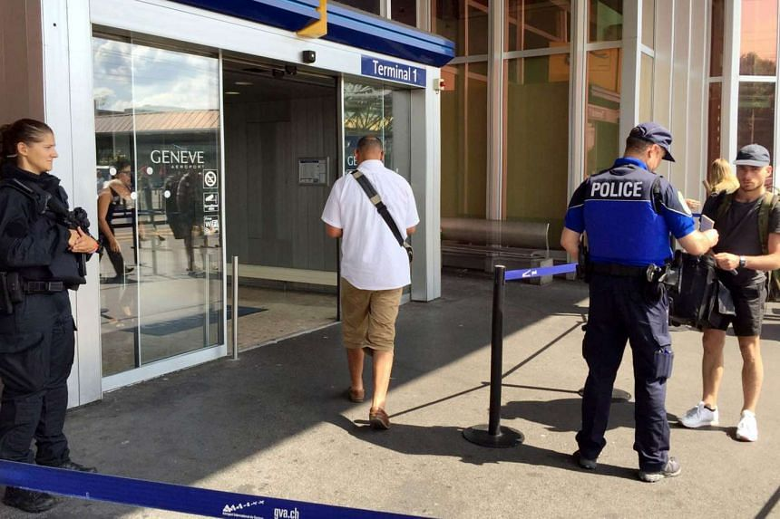 Swiss police officers conduct checks on passengers at the entrance of the Cointrin airport in Geneva, on July 27, 2016.