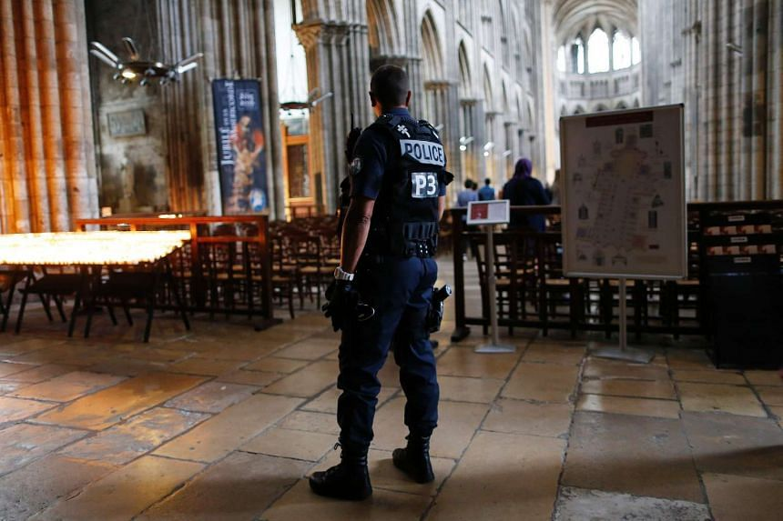 A policeman stands guard while people arrive for a mass at the Rouen Cathedral, on July 27, 2016.