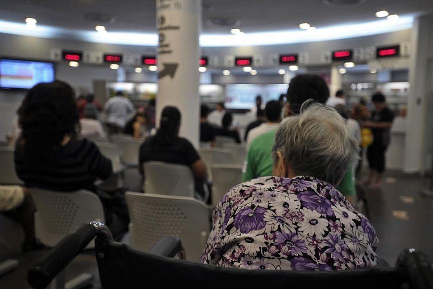 An elderly woman sits in the Pharmacy waiting area of Choa Chu Kang Polyclinic.