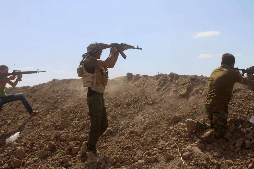 Iraqi pro-governement forces fire their weapons on a front line in the Albu Huwa area on May 31 during an operation aimed at retaking areas from the Islamic State group.