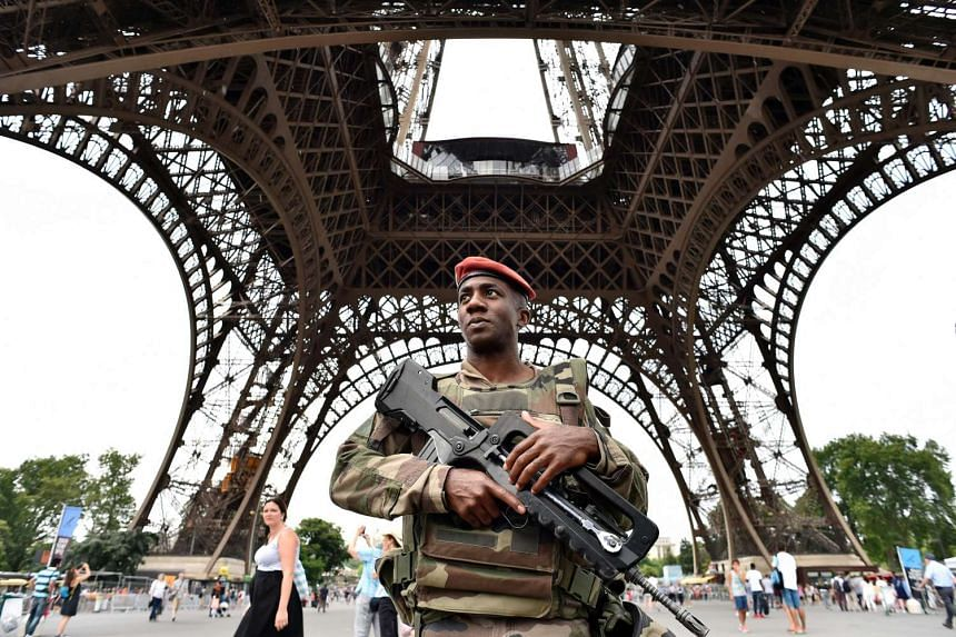 An armed French soldier patrols under at the Eiffel tower in Paris on July 20, 2016.