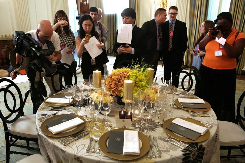 Journalists taking pictures of the table settings for the US-Singapore state dinner at the White House on July 29, 2016.