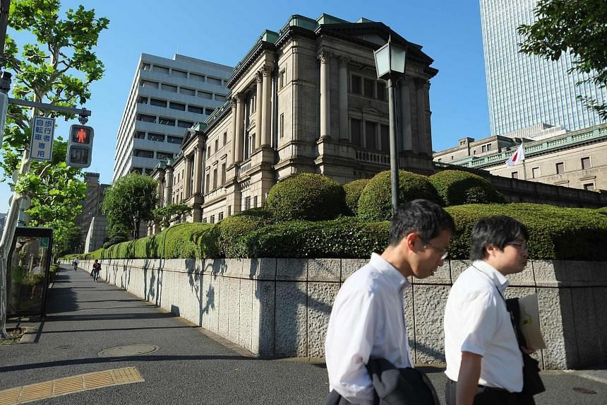 The BOJ's headquarters (above) in Tokyo. Mr Kuroda (left) and his team enlarged a programme of buying exchange- traded funds and expanded a US dollar-lending facility, but did not raise the target for the monetary base.