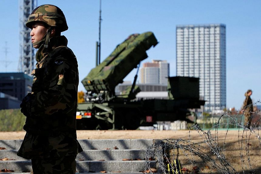 Members of the Japan Self-Defence Forces standing guard near PAC-3 land-to-air missiles, deployed at the Defence Ministry in Tokyo. The new upgrade could enhance the range and accuracy of the missiles needed to intercept North Korean ballistic missil