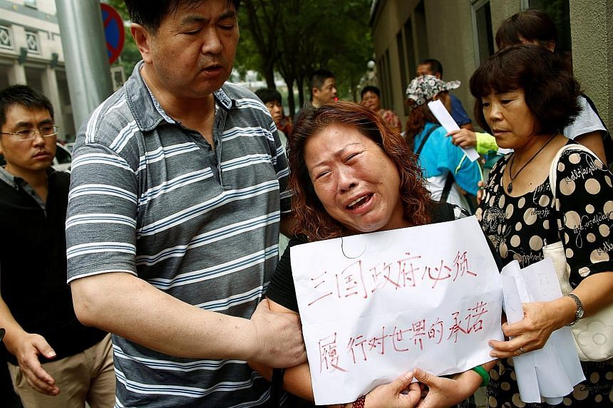 "A woman holding a sign saying ""The three governments have an obligation to carry out their promise to the world"" at the protest outside the Chinese foreign ministry in Beijing yesterday. About 30 family members gathered to hand over a petition for th"