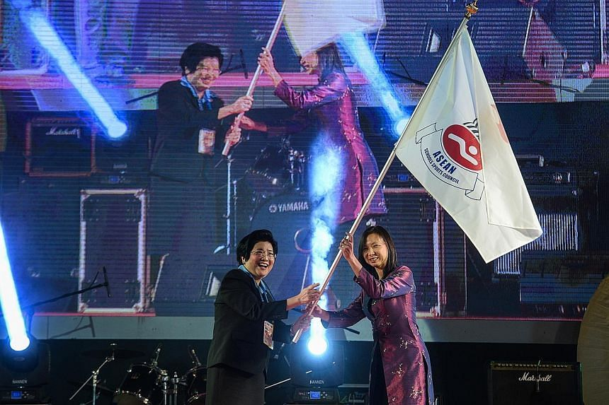 Thai associate professor Chavanee Tongroach (left), the president of the 8th Asean Schools Games organising committee, passes the Asean Schools Sports Council flag to Singapore's Liew Wei Li during the closing ceremony in Chiang Mai on Thursday. Sing