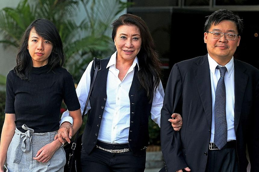 Shi (centre) leaving the State Courts with lawyers Melissa Kor and lrving Choh. She has been embroiled in a dispute with her neighbour over her raintree in Astrid Hill, and was ordered last week to pay $9,800 in damages to the neighbour and to trim t