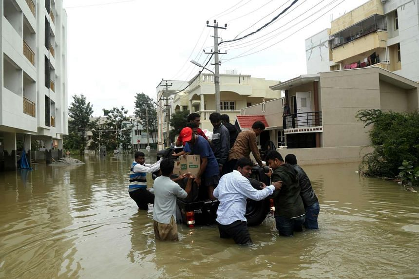 Indian Emergency Service personnel and fire fighters help people to reach safe areas during a flood in Bangalore on July 29, 2016.