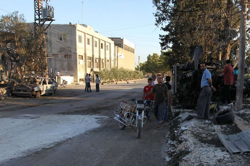People inspect the damage as they stand near the Save the Children-sponsored maternity hospital after the airstrike.