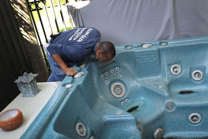 A Miami-Dade County mosquito control inspector, looks in a hot-tub for signs of mosquitos breeding in Florida on May 26, 2016.