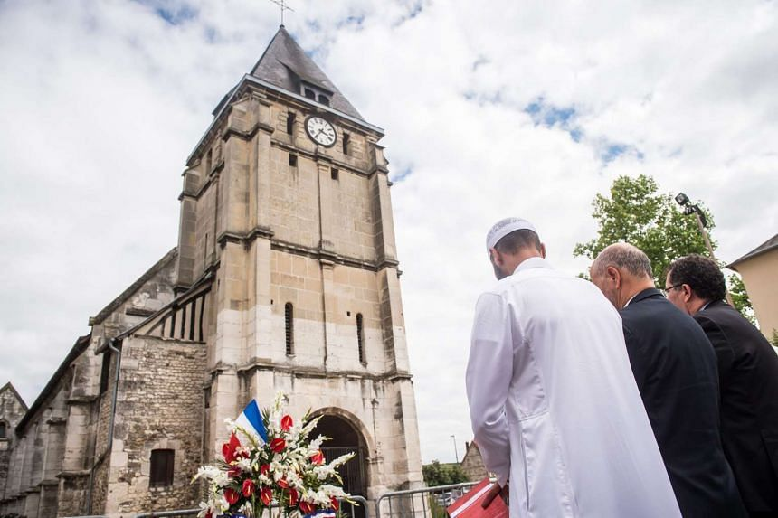 Muslim worshippers observe a minute of silence in front of the Saint Etienne church in Saint-Etienne-du-Rouvray, near Rouen, France, 29 July 2016.