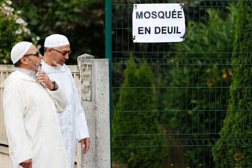 """People walk past a sign reading """"mosque in mourning"""" as they go to pray at the Yahya mosque on July 29, 2016, in Saint-Etienne-du-Rouvray, western France."""