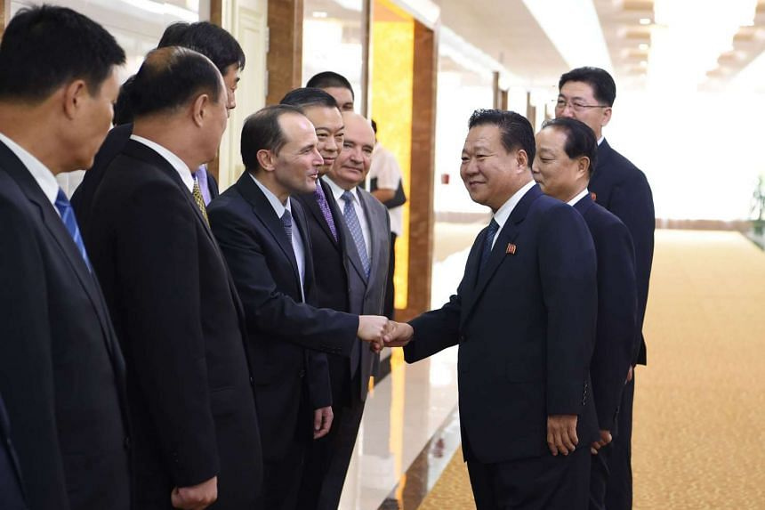 Delegation leader Choe Ryong Hae (centre) shakes hands with Brazil's representative Cleiton Schenkel before leaving Pyongyang.