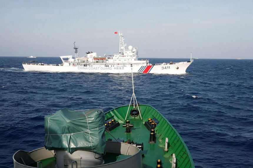 A ship (top) of the Chinese Coast Guard is seen near a ship of the Vietnam Marine Guard in the South China Sea in May 2014.