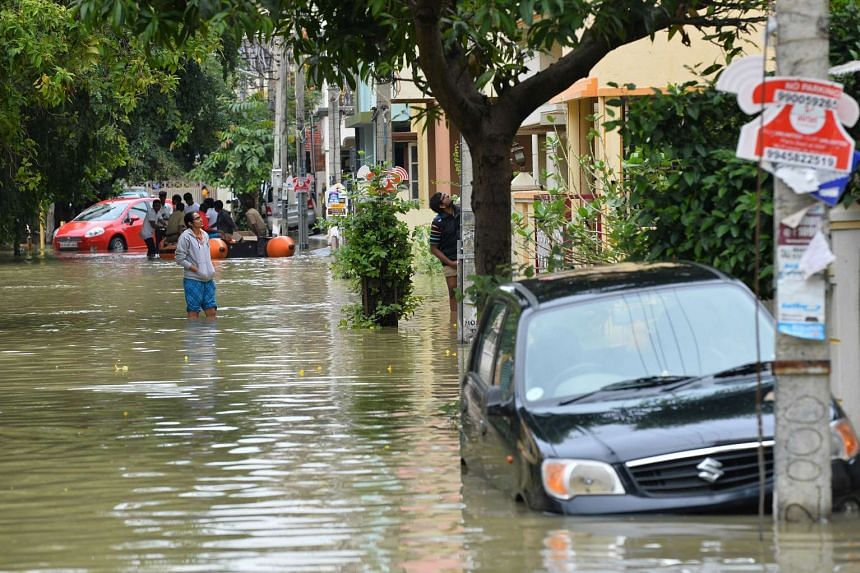 Residents wade through knee deep water during relief operations in a low lying flooded area of Bangalore on July 29, 2016 following continuous rains.