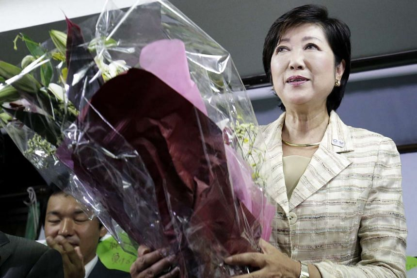 Japan's Former Defense Minister Yuriko Koike (centre) holds a bouquet of flowers as she celebrates her victory in the Tokyo Gubernatorial Election at her election campaign office on July 31, 2016.