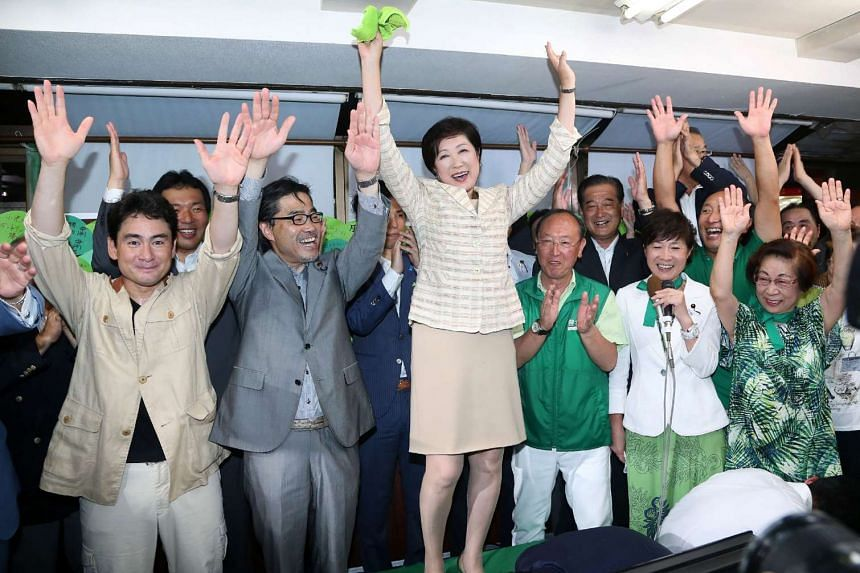 Former Japanese defence minister Yuriko Koike (centre) and supporters celebrate her win as Tokyo governor, in Tokyo on July 31, 2016.
